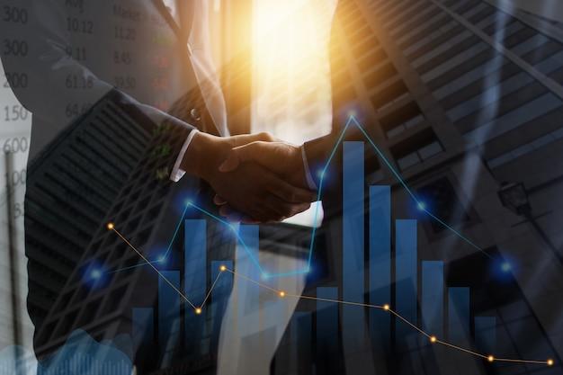 Succès et réussite de la négociation d'un accord, les hommes d'affaires se serrent la main et coopèrent pour investir dans les affaires, gros plan sur la poignée de main des hommes d'affaires avec un graphique boursier et des données forex