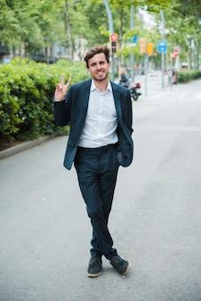 Succès souriant jeune homme d'affaires debout sur la rue montrant le signe de la victoire