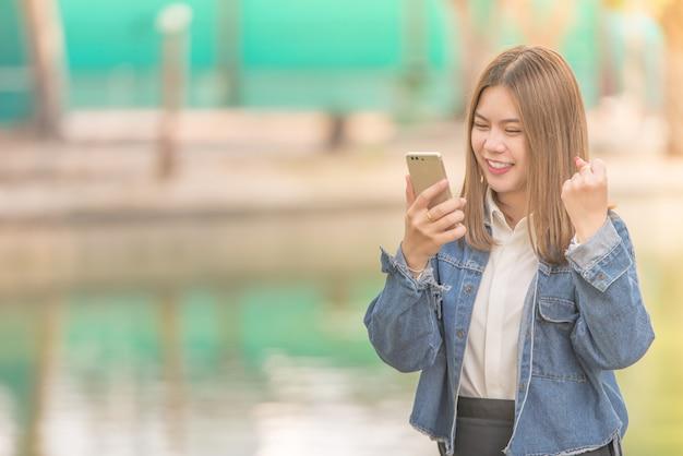 Succès et surpris jeune femme asiatique en utilisant un téléphone intelligent à l'extérieur