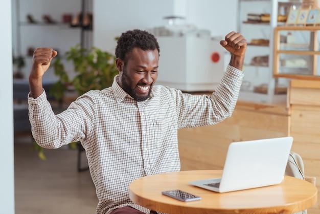 Succès tant attendu. heureux jeune homme assis à la table dans le café et levant les mains pour célébrer après que son programme commence à fonctionner avec succès