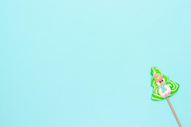 Sucette de bonbons de bonhomme de neige drôle et arbre de noël sur fond bleu. disposition créative lumineuse pour noël, nouvel an