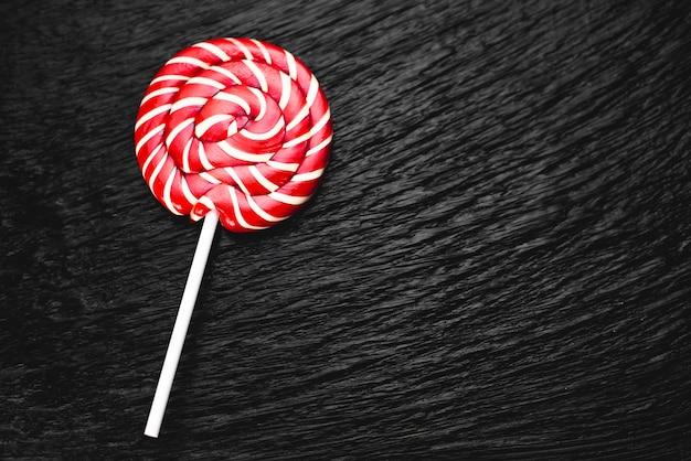 Sucette de couleur rouge, ronde sur fond noir doux