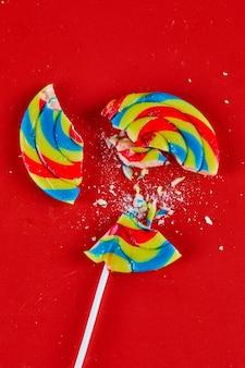 Sucette craquelée colorée sur une surface rouge.