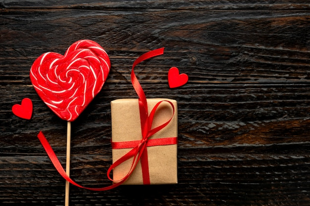 Sucette en forme de coeur et boîte-cadeau artisanale pour la saint-valentin sur fond de bois foncé. concept festif, vue de dessus.