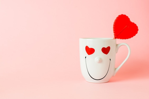 Sucette en forme de coeur doux rouge dans une tasse avec un visage souriant