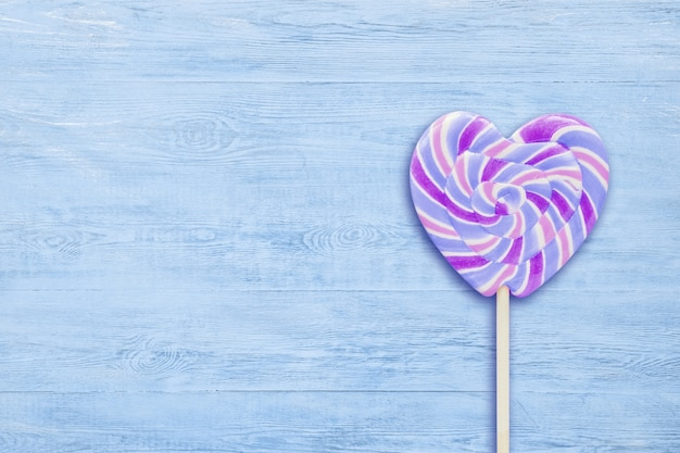 Sucette en forme de coeur à rayures bleues sur fond de copie en bois bleu.