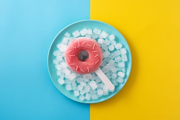 Sucette glacée aux fraises et glace pilée sur table jaune et bleue