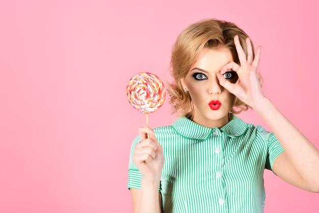 Sucette. nourriture sucrée, dessert, sucre et concept de plaisir. beau modèle pin up avec sucette à la main. fille sexy de mode rétro drôle dans un style estival avec des bonbons colorés. copiez l'espace pour la publicité.