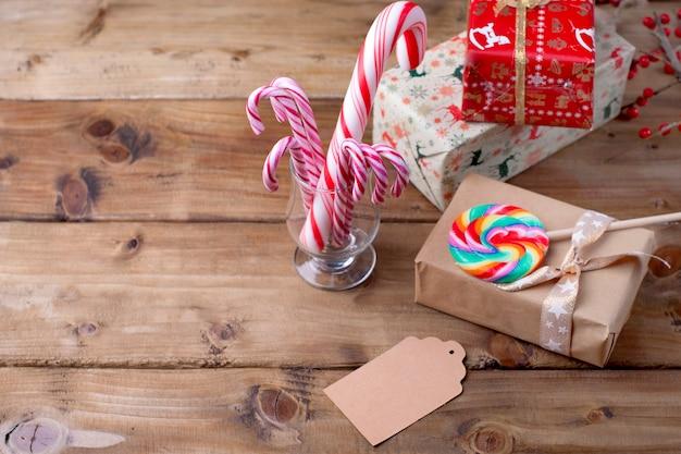 Sucette à rayures lumineuses et un cadeau sur une table en bois et une branche de fruits rouges