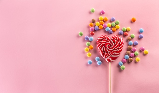 Sucette rouge à rayures en forme de cœur entourée de bonbons colorés sucrés posés sur le fond rose.