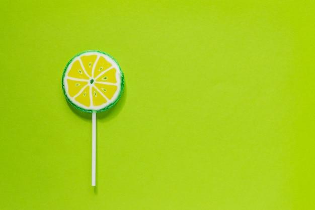 Sucette savoureuse sucrée en forme de tranche de citron vert. mise à plat minimale avec espace de copie