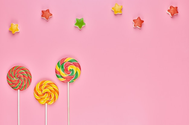 Sucette sucrée et bonbons sur fond rose