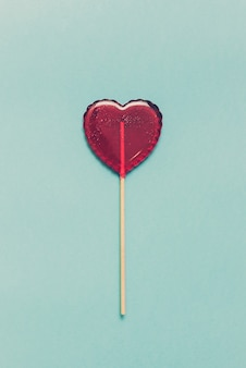 Sucette sucrée sur fond bleu. coeur rouge. bonbons. concept d'amour. saint valentin