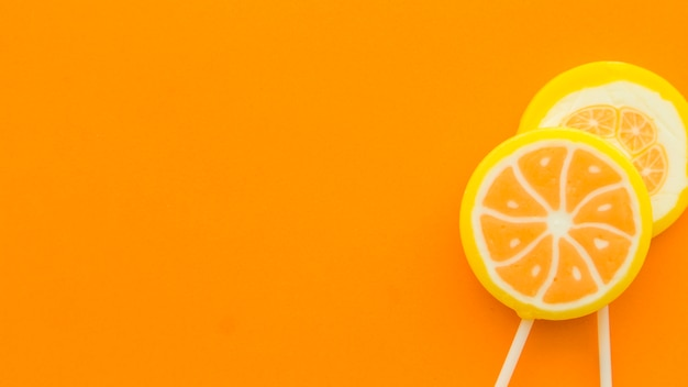 Sucettes d'agrumes fraîches sur fond orange