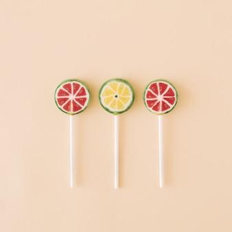 Sucettes aux fruits qui font face à des pastèques et des citrons verts sur un fond crème concept d'été alimentaire