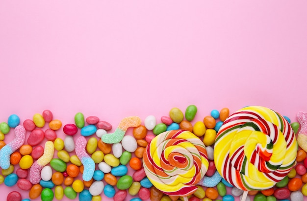 Sucettes colorées et bonbons ronds de couleurs différentes sur rose