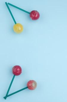 Sucettes colorées sucrées isolés sur fond bleu. concept de sucette. copier l'espace pour le texte.