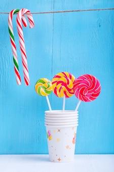 Sucettes dans une tasse et des cannes de bonbon suspendues à un fil