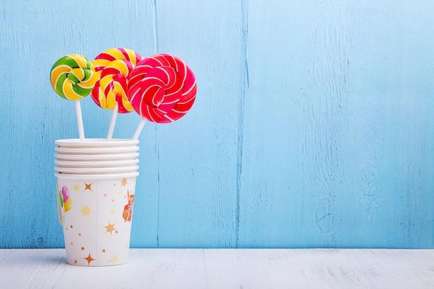 Sucettes dans des tasses sur un mur en bois bleu