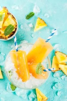 Sucettes glacées à l'ananas maison sur glace avec des tranches d'ananas frais et de la menthe