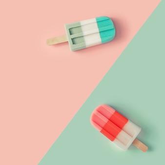 Sucettes glacées aux couleurs pastel rose et bleu sur papier bichromie. concept d'été minimal.