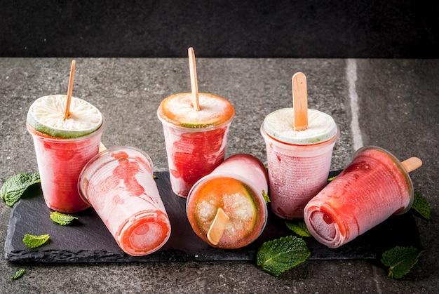 Sucettes glacées maison. boissons glacées. cocktail congelé de pastèque ou de petits fruits, menthe et citron vert.