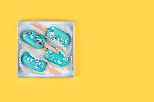 Sucettes glacées à la menthe bleue dans une boîte en papier sur jaune.