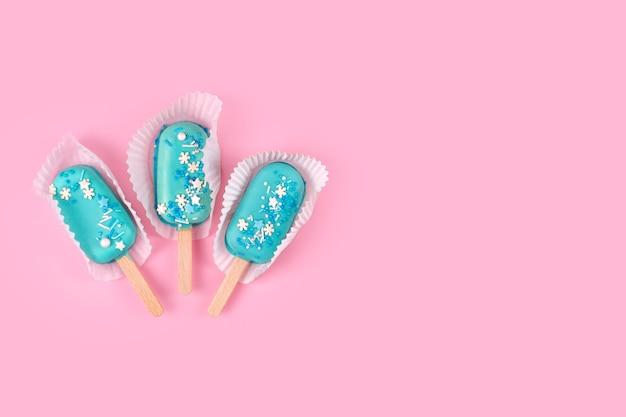 Sucettes glacées à la menthe bleue sur fond rose pastel. glace savoureuse et rafraîchissante sur bâtonnets. concept d'été minimal. fond plat et gratuit pour le texte