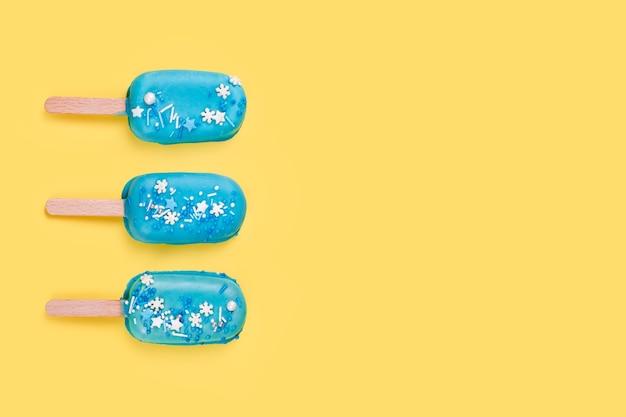 Sucettes glacées à la menthe bleue sur jaune.