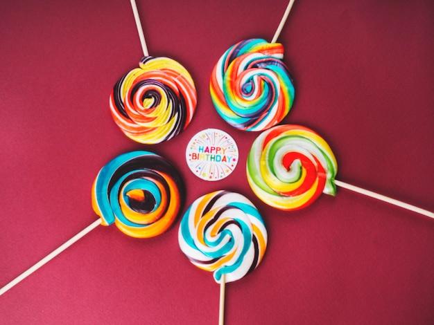 Sucettes multicolores et signe de joyeux anniversaire