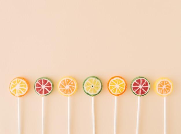 Sucettes qui font face à des pastèques oranges citrons et limes sur un concept alimentaire de fond crème
