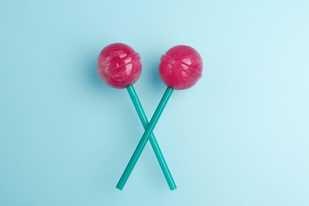 Sucettes roses sur fond bleu pastel. concept de sucette sucrée.