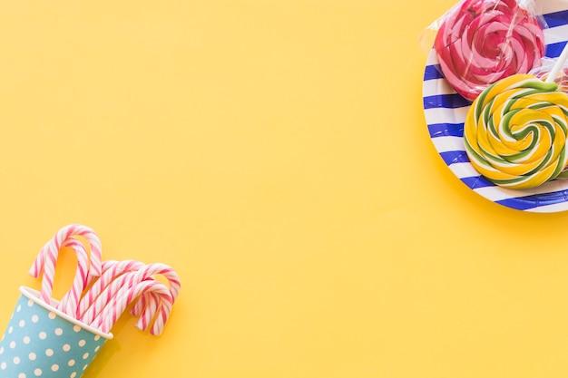 Sucettes de sucettes et cannes de bonbons de noël en gobelet jetable sur fond jaune