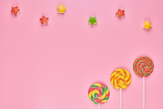 Sucettes sucrées et bonbons isolés sur rose