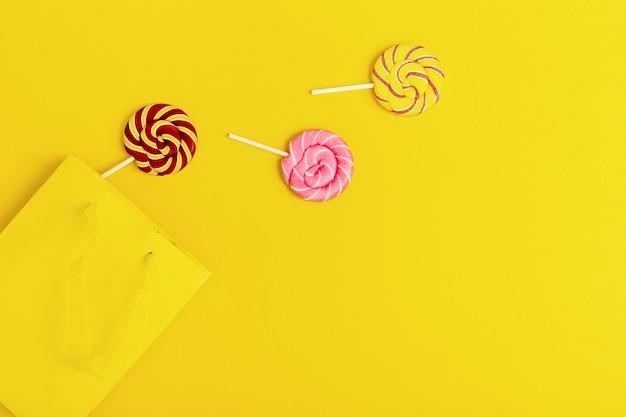 Sucettes sucrées rondes avec des rayures sur bâton hors du papier jaune. concept créatif échapper à la liberté pour anniversaire, fête, vacances.