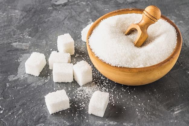 Sucre blanc dans une assiette en bois avec une pelle sur un fond sombre, des cubes de sucre.