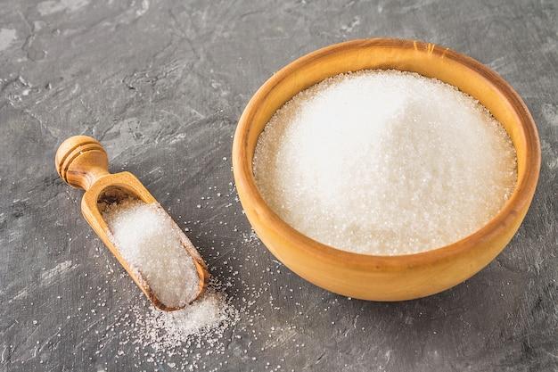 Sucre blanc dans une assiette en bois avec une pelle à poussière sur un fond sombre.