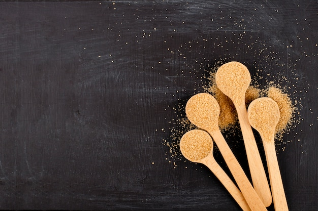 Sucre de canne brun dans quatre cuillères en bois sur fond noir.