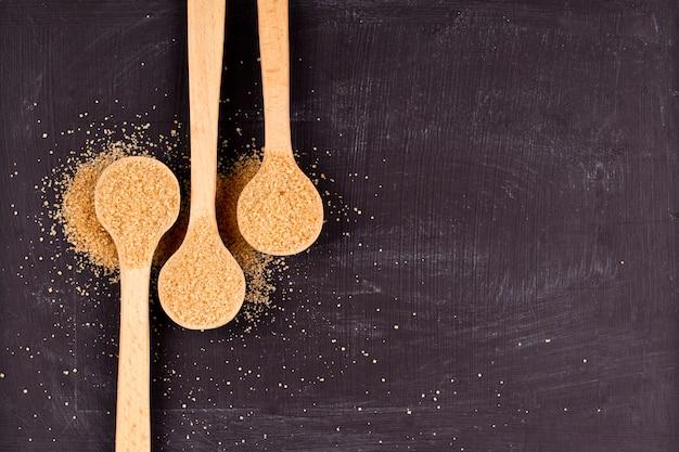 Sucre de canne brun dans trois cuillères en bois sur fond noir.