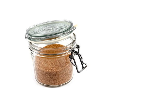 Sucre de canne brun en pot de verre isolé sur fond blanc.