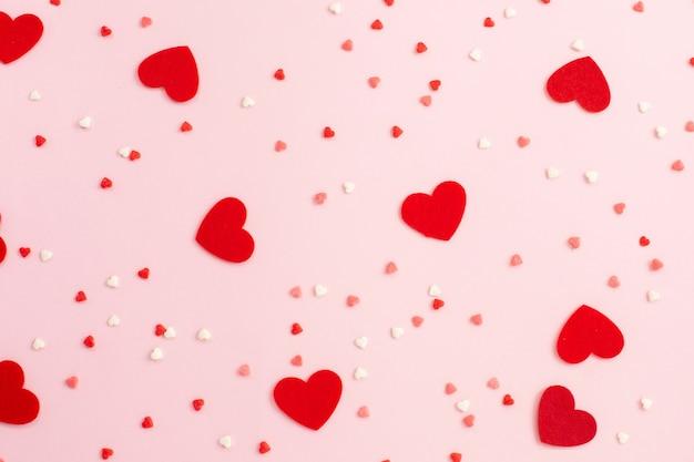 Sucre et coeurs en feutre sur fond rose. romantique,