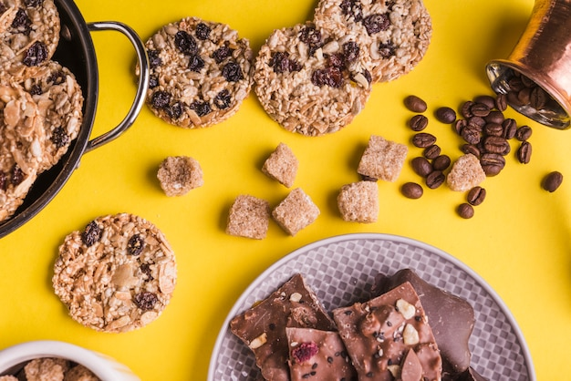 Sucre en cubes; cookies au chocolat; grains de café et plaque de barres de chocolat sur fond lumineux jaune