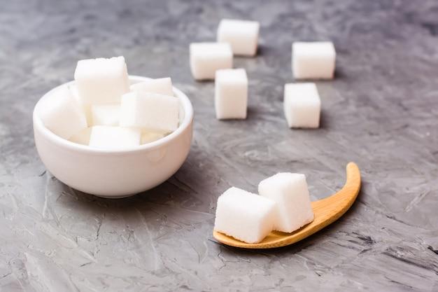 Sucre cubes dans un bol blanc et une cuillère en bois sur une table