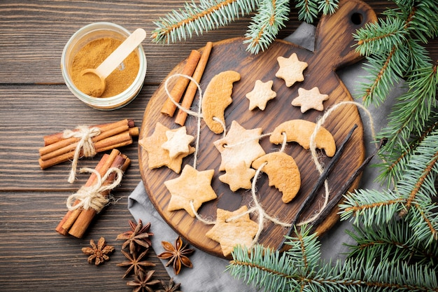 Sucre en forme d'étoile sablé fait maison avec du sucre en poudre et branche de fit-tree sur bois brun