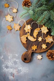 Sucre en forme d'étoile sablé fait maison avec du sucre en poudre et branche de fit-tree sur le fil sur la surface de texture bleue. focus sélectif. noël ou nouvel an.