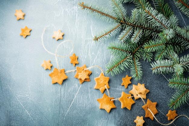 Sucre en forme d'étoile sablé fait maison avec du sucre en poudre et branche de fit-tree sur le fil sur la surface de texture bleue. noël ou nouvel an. vue de dessus avec espace.