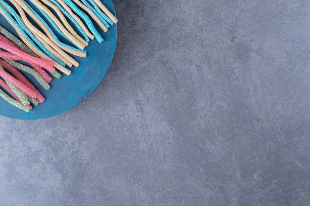 Sucre en poudre sur des bonbons à la réglisse sur une assiette sur une table en marbre