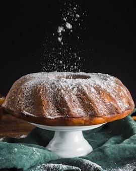 Sucre en poudre coulant sur le gâteau