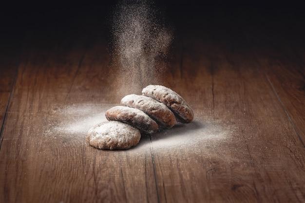 Le sucre en poudre est jonché sur des biscuits faits maison sur une table en bois