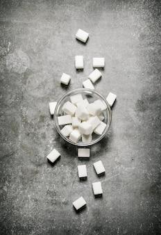 Sucre raffiné dans une soucoupe en verre. sur un fond de pierre.